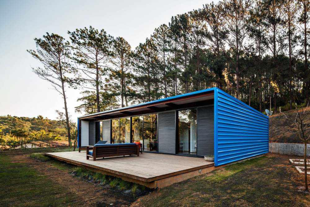 The house has a simple rectangular shape with blue metal panels framing it and giving it character