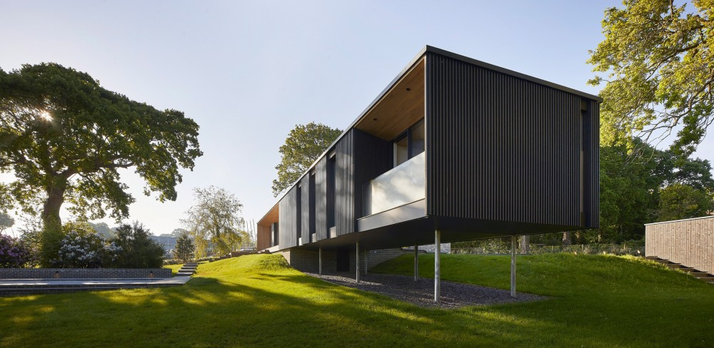 The house is partially suspended on slender stilts in response to the topography and flooding risk in the area