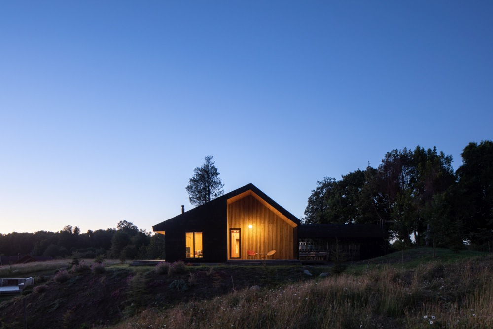The dark exterior and warm wooden interior complement each other and bring the house closer to its surroundings