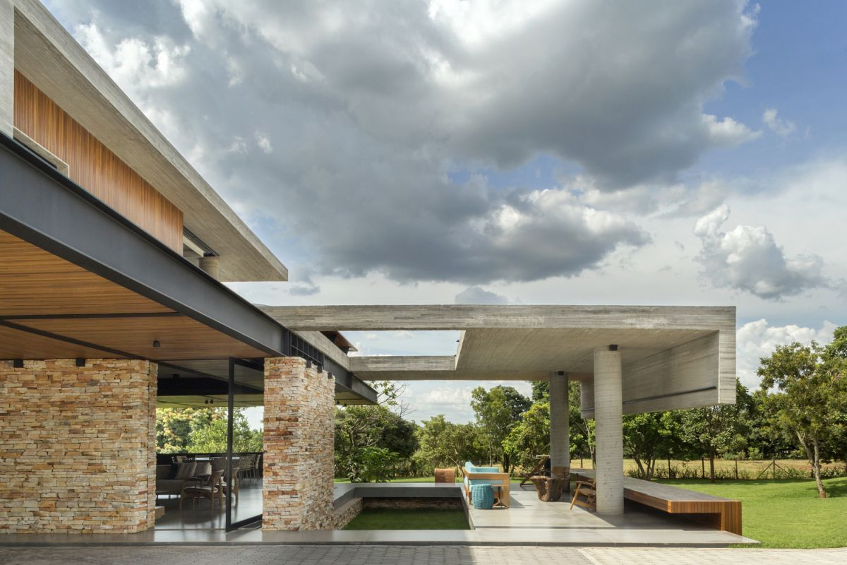 The rough stone blends well with the concrete and the wood, serving as an intermediary between the other materials