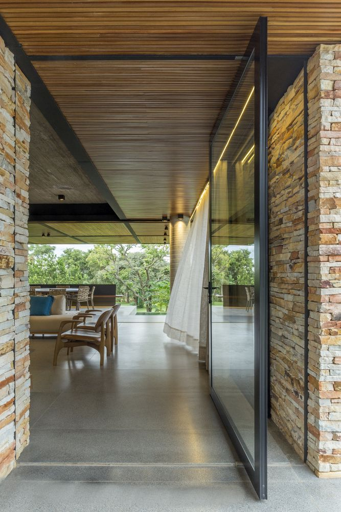 A large glass door marks the main entrance and leads into the living area, with a direct view through the whole volume