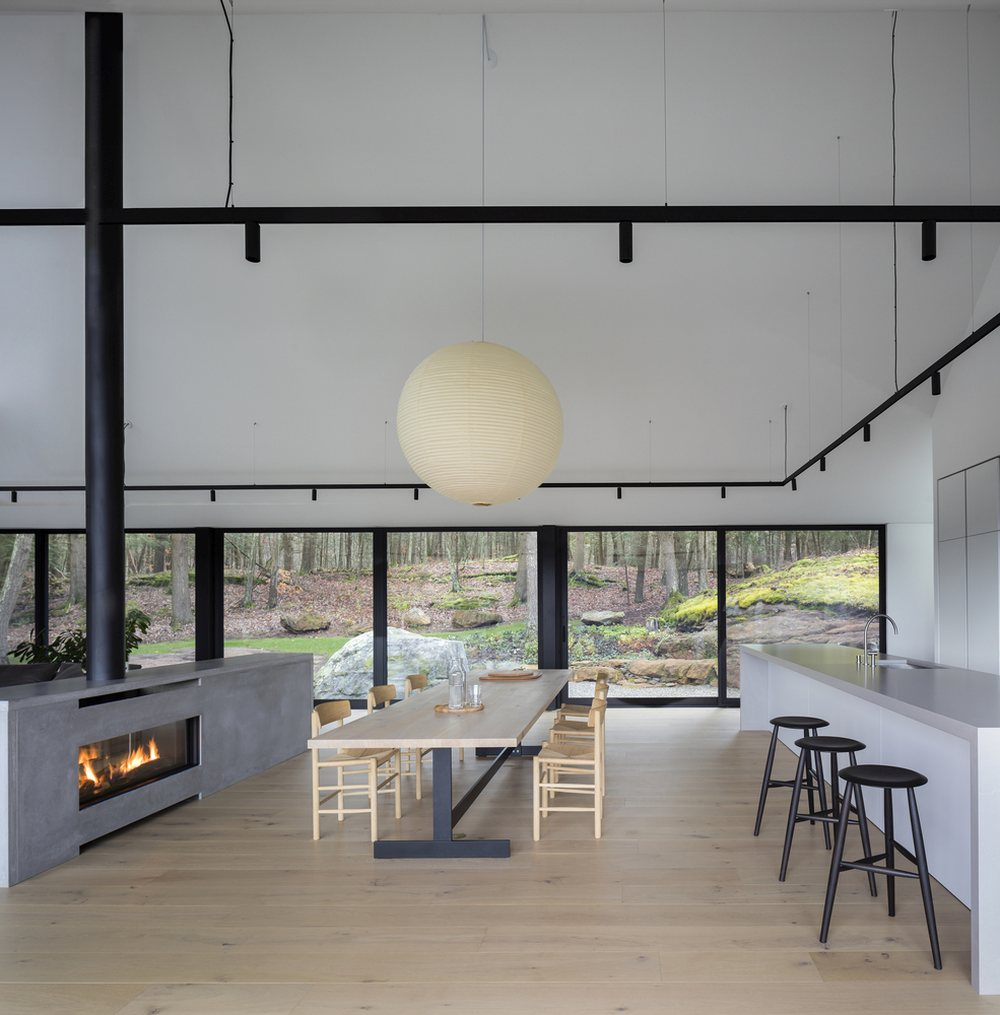 The eat-in kitchen and the living area are divided by a minimalist two-sided fireplace