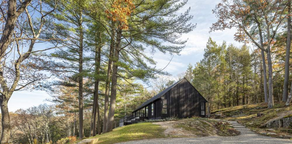 The house sits on top of a rock ledge, with a beautiful forest on one side and a stunning valley on the other