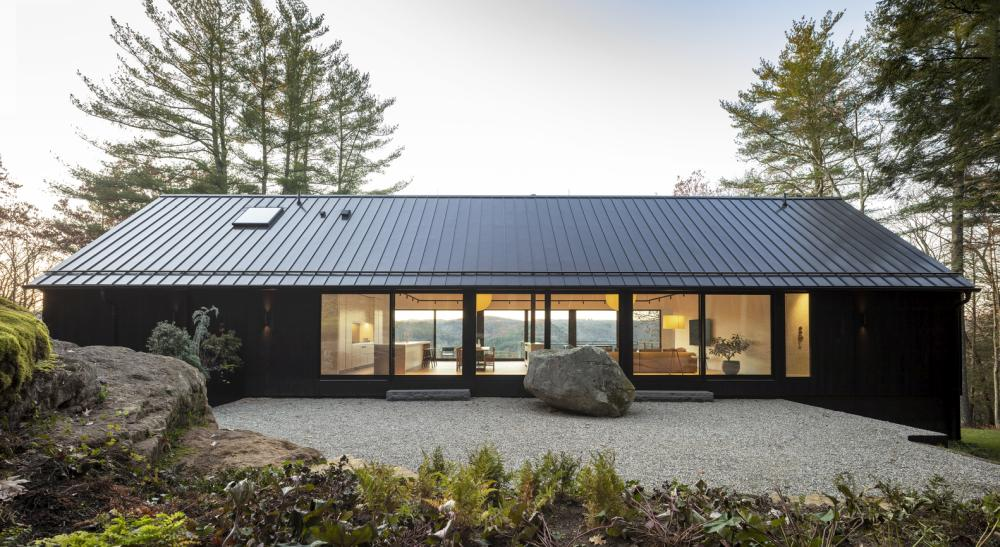 The overall design of the house is fairly symmetrical, featuring large openings on opposite walls