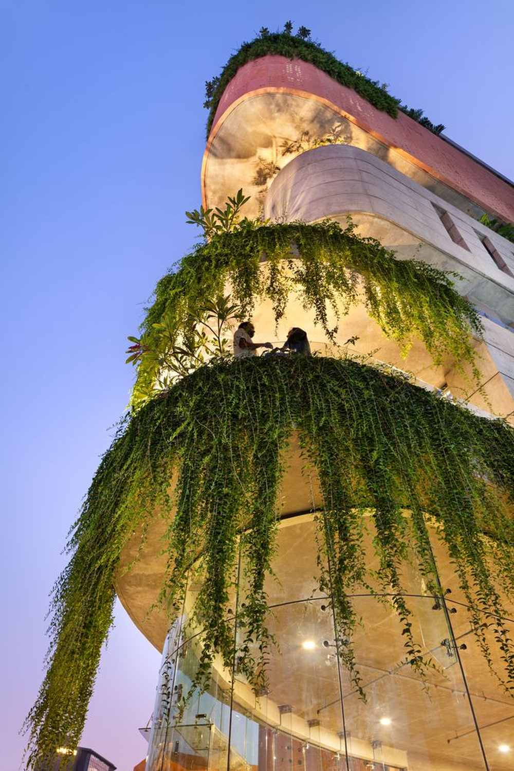 The cantilevered sections have balconies with greenery flowing down from them
