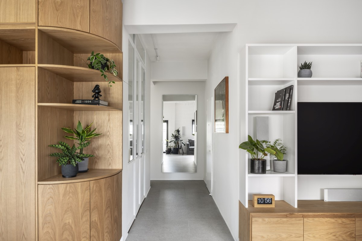 A bright corridor separates two different sections of the apartment, the private and the public areas