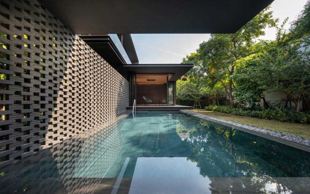 The swimming pool is sheltered underneath the cantilevered house and framed by a perforated wall and a lovely garden