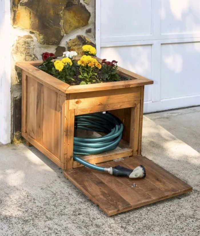 Wooden planter box with a built-in hose holder