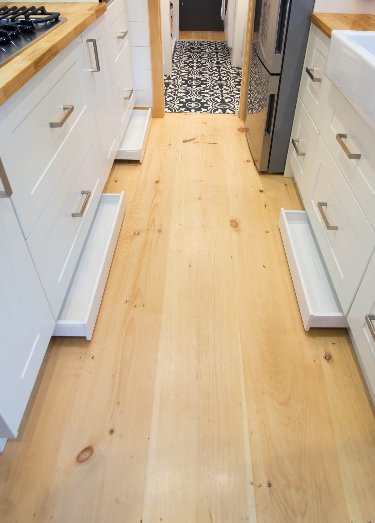 Clever pull-out trays add additional storage to the very bottom section of the kitchen cabinets
