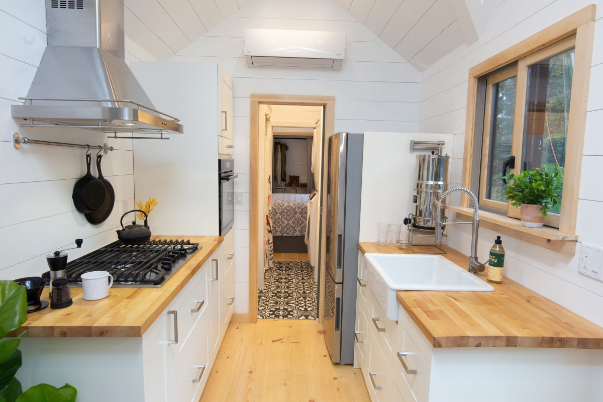 The bathroom is positioned past the kitchen, at the very end and has a stylish black and white tiled floor