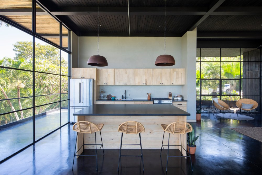 The kitchen, dining area and living room share an open floor plan with full-height windows and a minimalist design