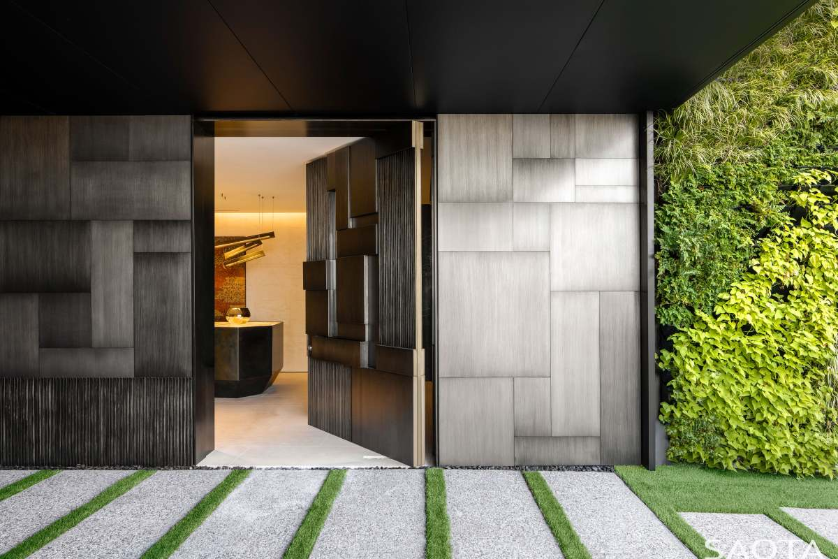 The main entrance is marked by a clean and minimalistic pathway and a large door with a 3D design