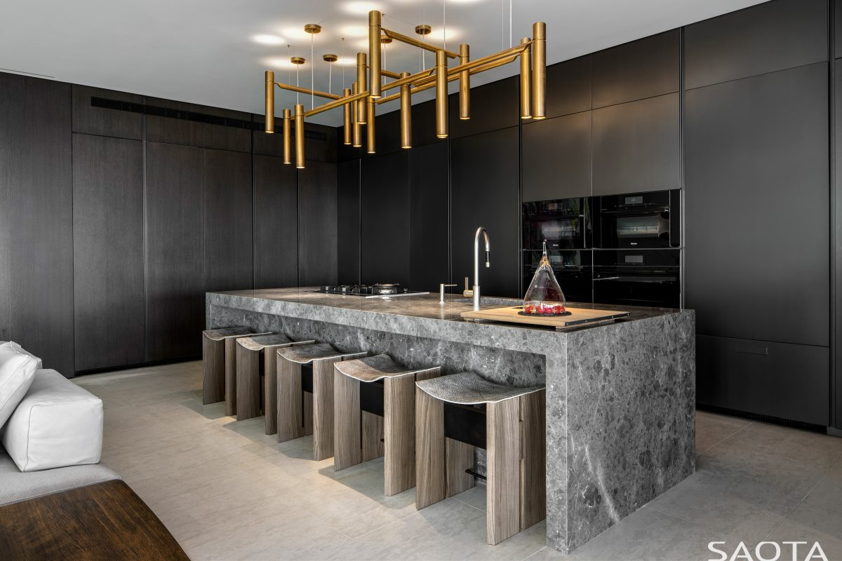 The kitchen is minimalistic and has all black cabinetry along the walls