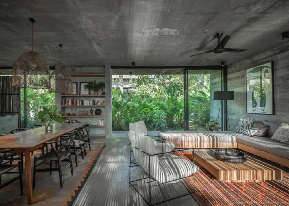 The living room, dining area and the kitchen are combined into a large volume with an exposed concrete ceiling and full-height windows