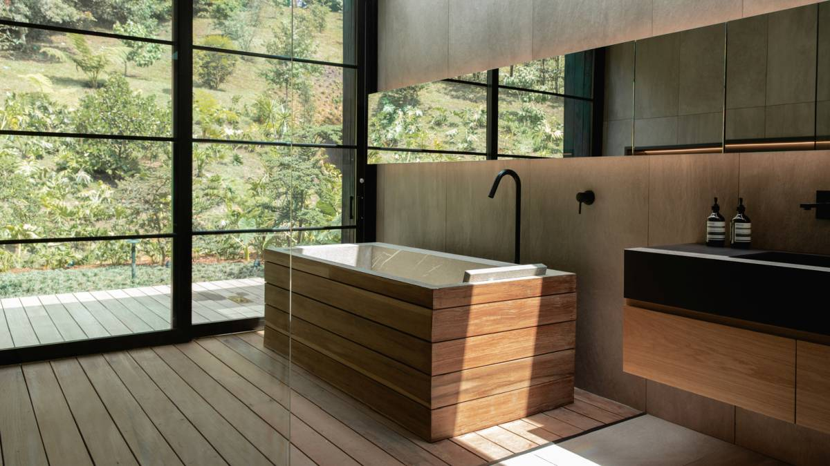 The bathroom has large windows that expose it to the outdoors and that bring in lots of natural sunlight