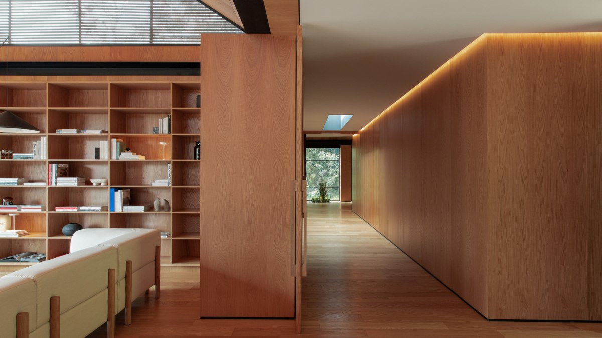 A minimalist wooden corridor connects the interior spaces and runs across the entire house