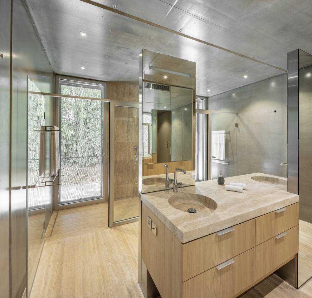The bathroom enjoys a very airy interior with large windows and an open concept layout