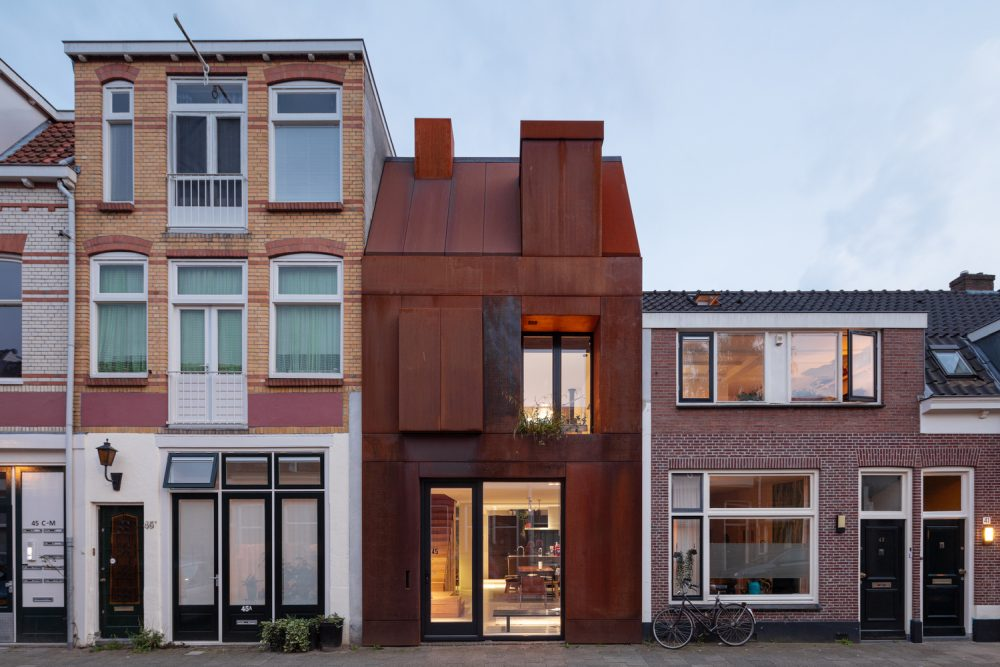 The house is tall and narrow and sits flush with the two existing buildings on either side of it