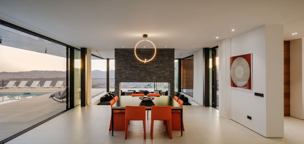 The dining area is at the center of the social area and adds a splash of color to the ground floor with its stylish orange chairs