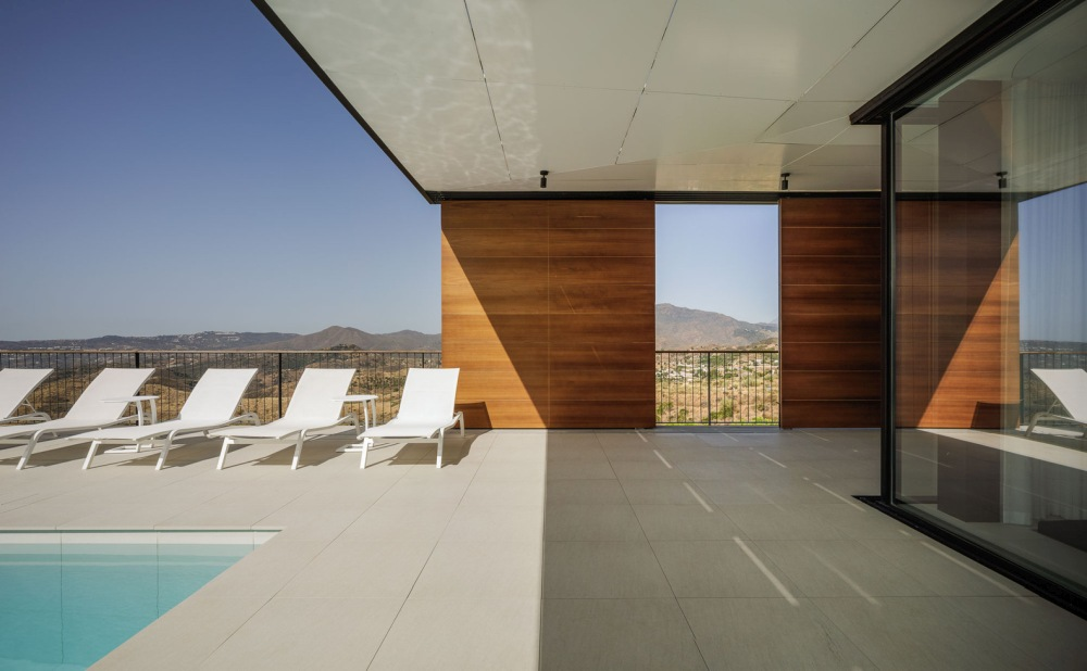 A series of sliding shutters made of oak wood regulate the sunlight and exposure of the outdoor spaces