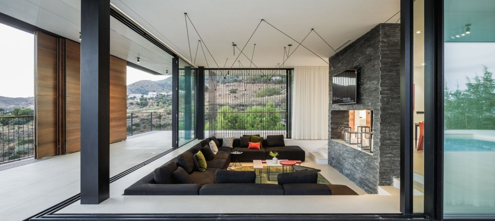 Sculptural metal light fixtures adorn the ceiling in the living room and maintain a minimalist decor