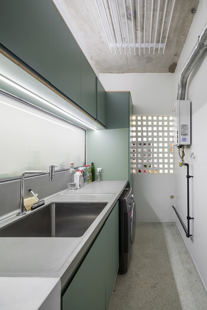 The laundry room has a bright and clean aesthetic similar to that of the kitchen