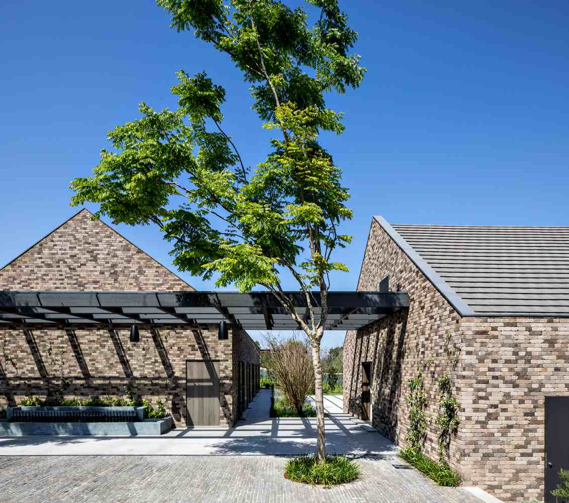 A black pergola roof stretches out and attached to two of the buildings creating a courtyard area