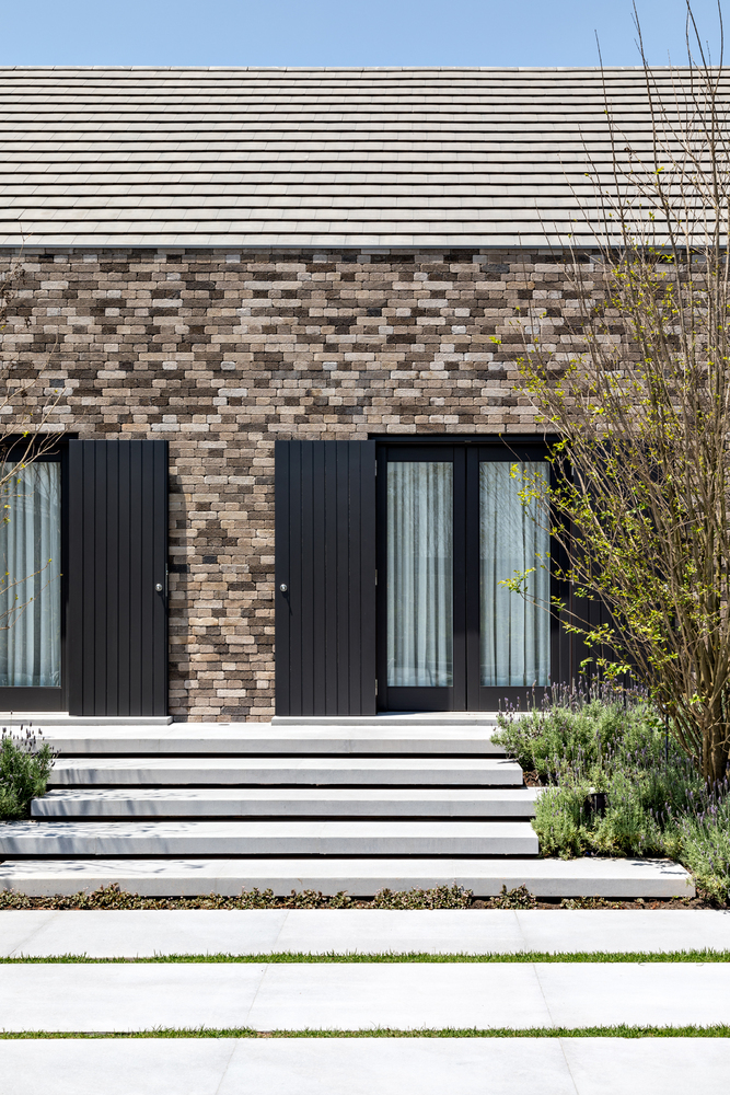 The doors and windows have black wooden shutters that can completely close off the house when needed