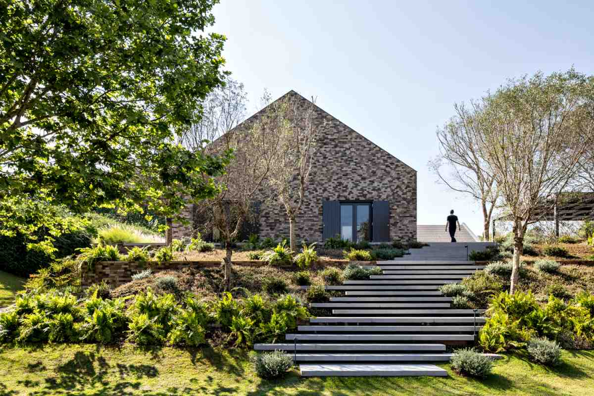 A minimalistic set of offset stairs gently go up the slope and bring the house into view