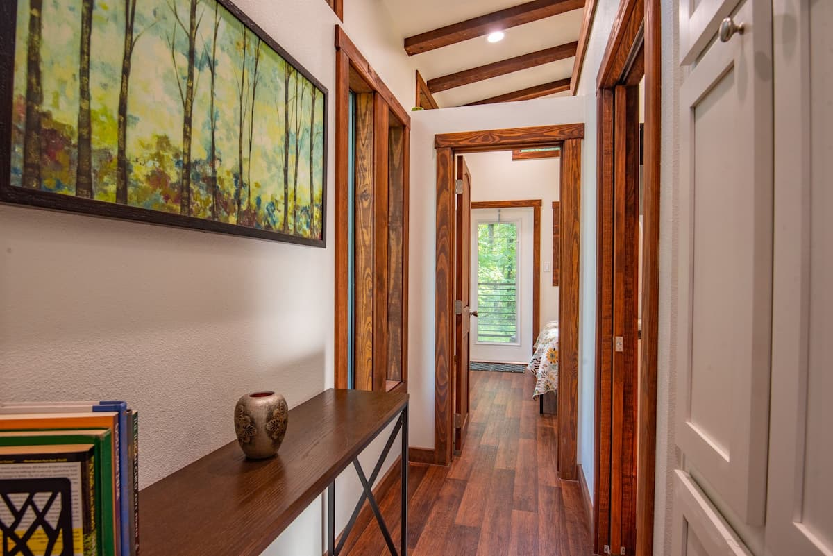 A small hallway with a console and artwork on the wall leads into the private areas