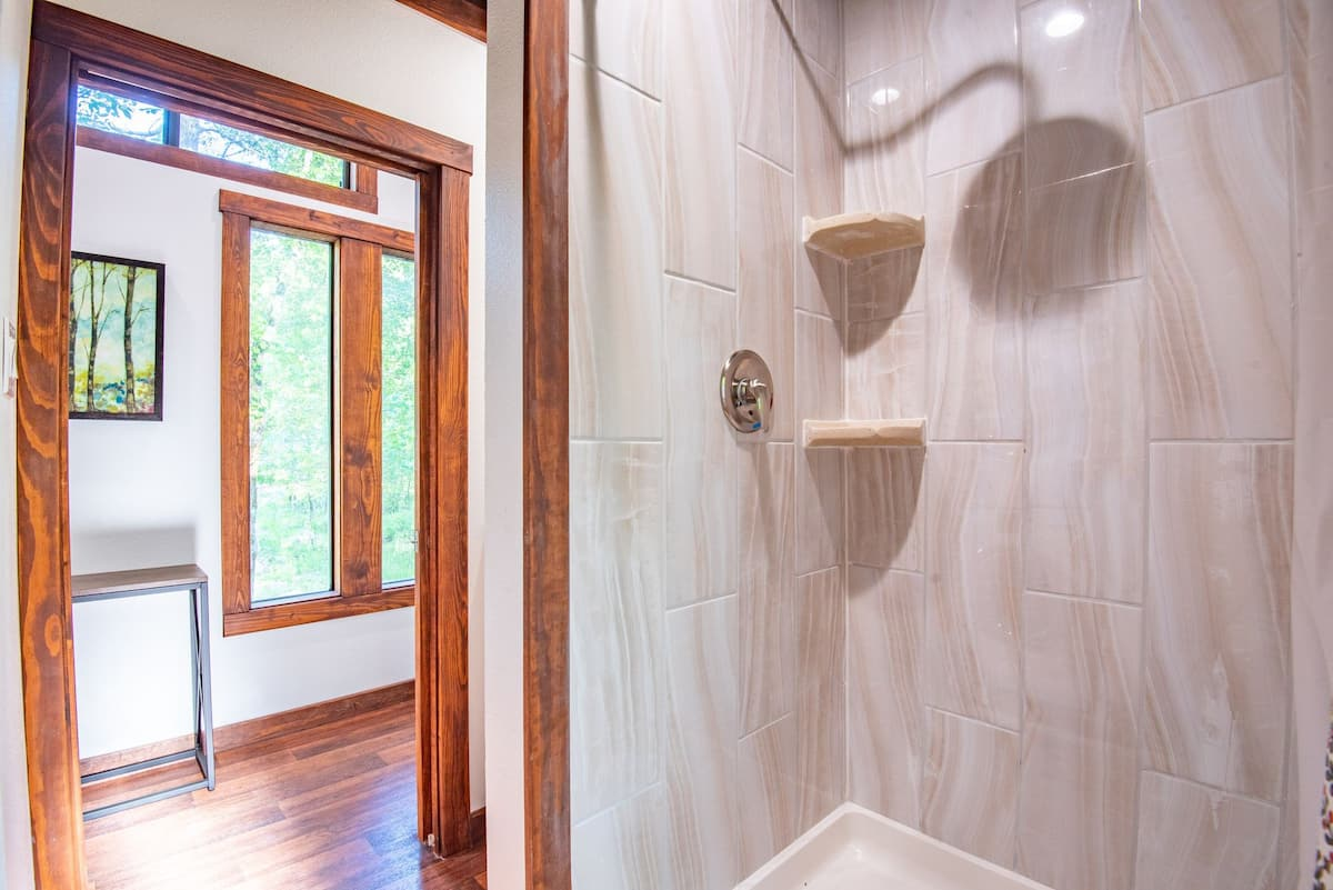 The hallways also leads into the bathroom which has a tiled shower in the corner