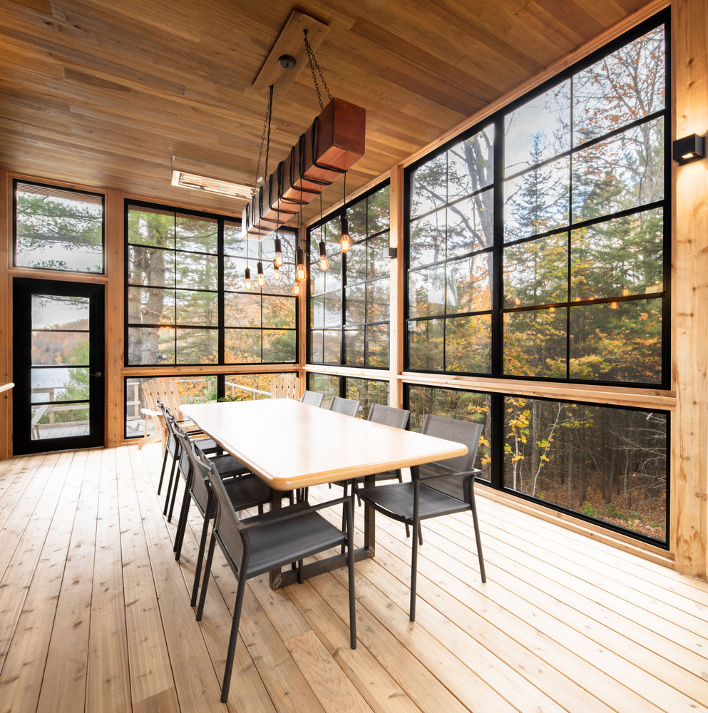 The dining table is framed by big windows that bring the outdoor beauty inside