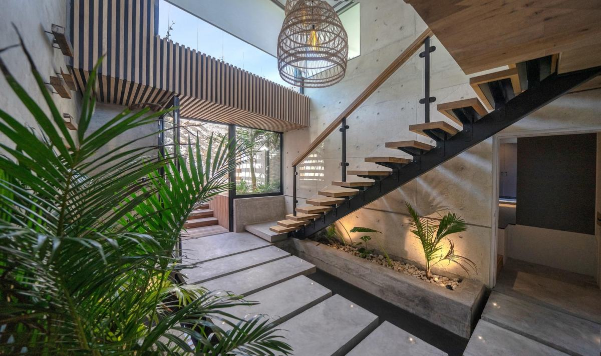 The staircase hall has courtyard-inspired feel, with lots of greenery and a very open feel
