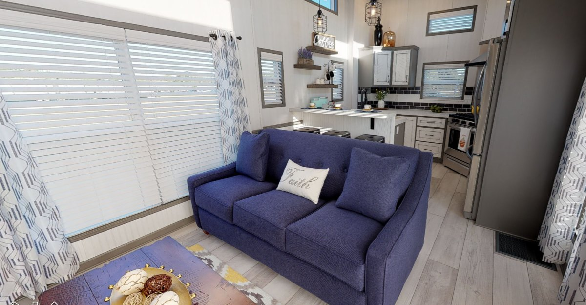 The living room sofa doubles as a divider between this area and the kitchen just behind it
