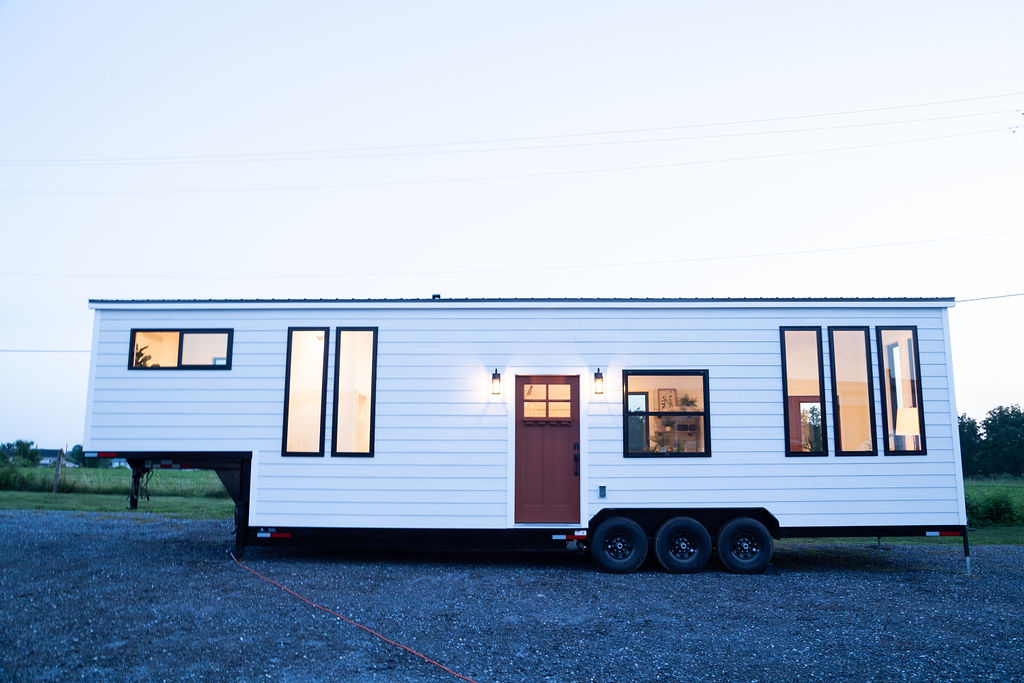 The Gooseneck tiny home on wheels has a very simple and clean design on the outside, with an almost flat roof and white facades