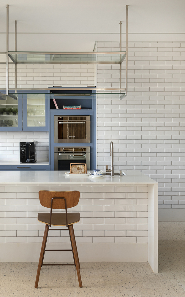 The kitchen has a very bright and open feel thanks to the white subway tiles and blue accents