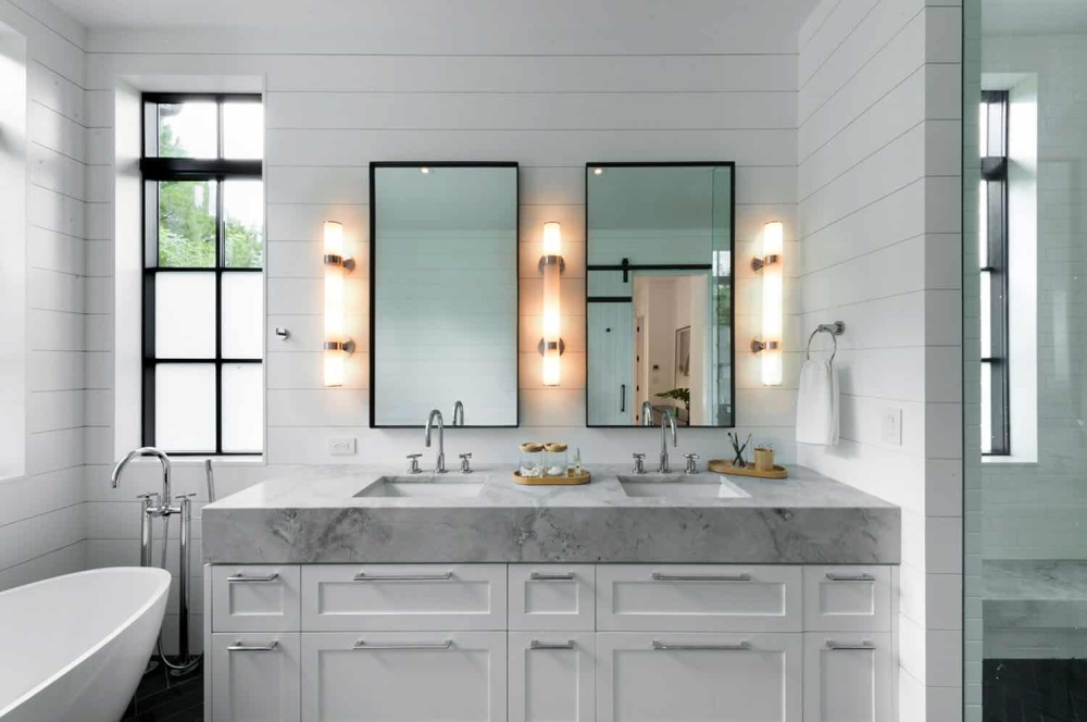 A double sink vanity with a beautiful light gray top adds a bit of farmhouse charm to the bathroom
