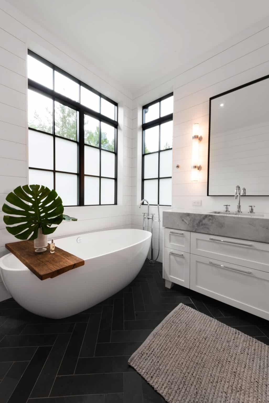 An oval soaking tub is placed at the far end of the bathroom, where it's framed by both windows