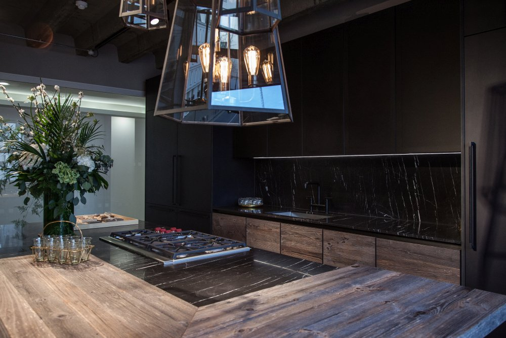 Modern kitchen design featuring black marble and unfinished wood for doors black cabinets