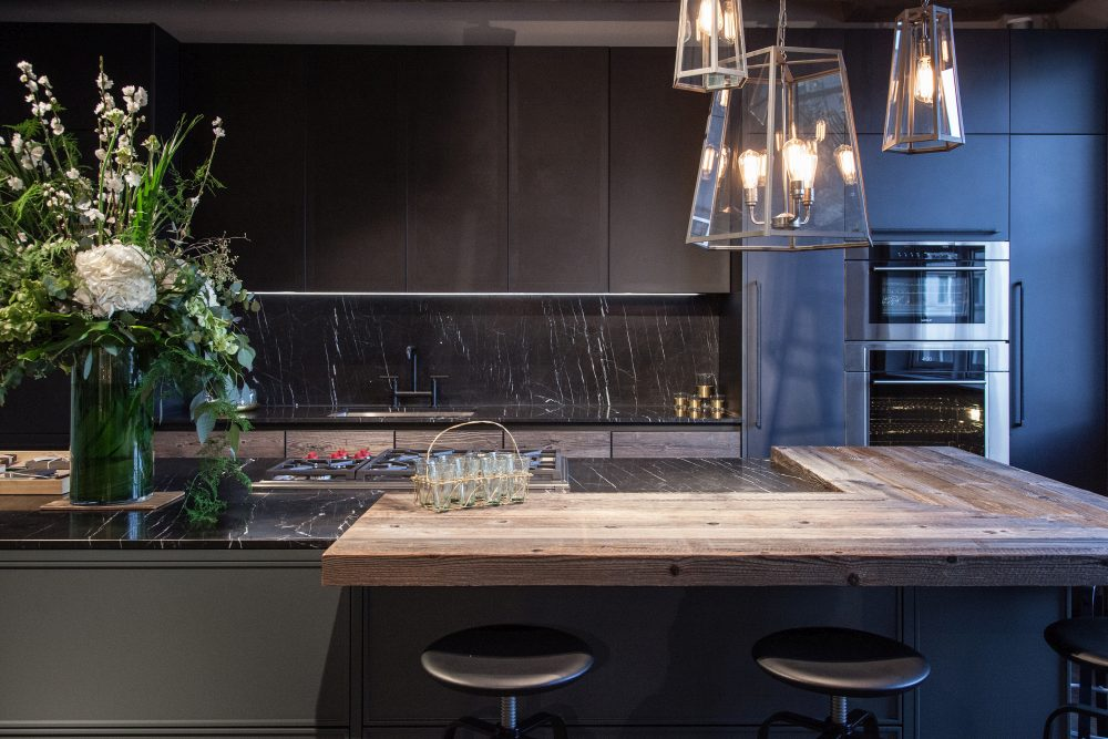 Modern kitchen design featuring black marble and unfinished wood for doors countertop