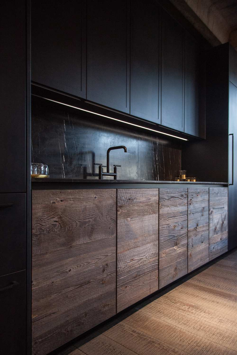 Modern kitchen design featuring black marble and unfinished wood for doors lower cabinets
