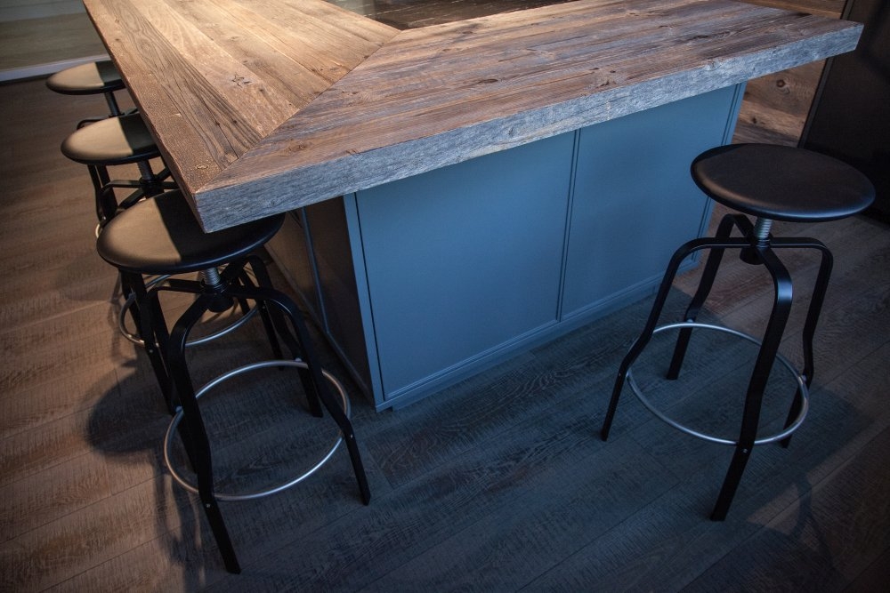 Modern kitchen design featuring black marble and unfinished wood for doors stools