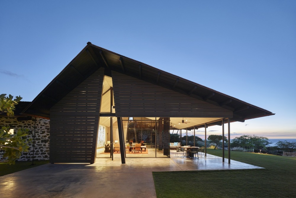 A series of thin steel column support the extended roof and form a covered patio just outside the main living area