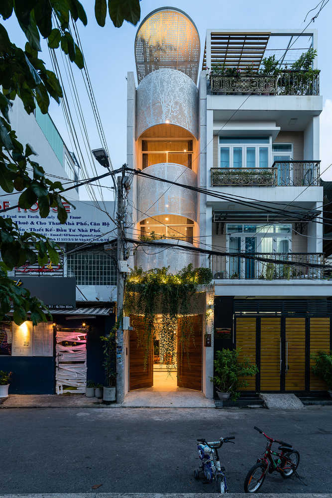 The perforated metal screens that frame the balconies turn this into a very interesting house