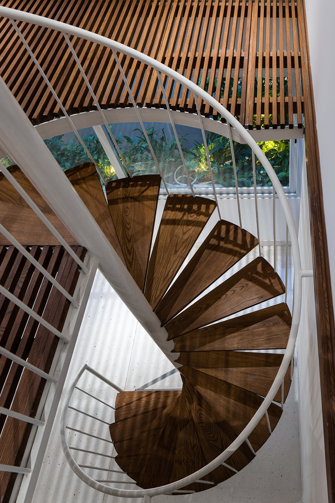 A spiral staircase made of wood and metal connects the floors at the core of the house