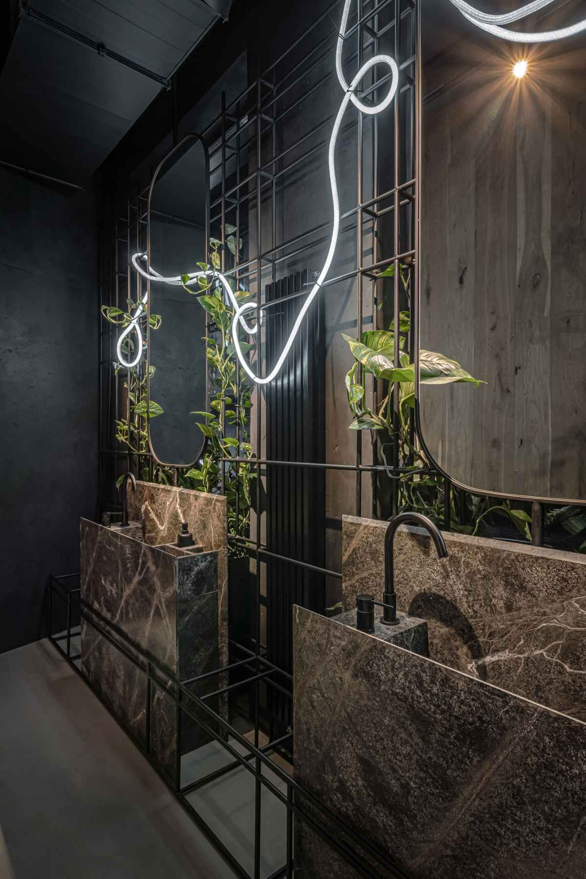 The lighting in the restroom is in the form of a slender tube that bends and twists adding a playful touch to the decor