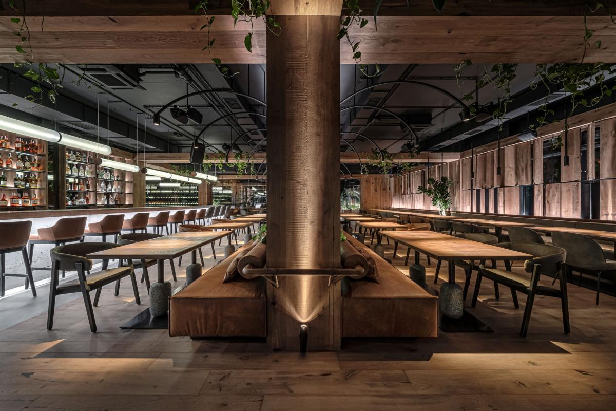 The main area is a large and open space with a tall black ceiling and robust wooden beams and columns