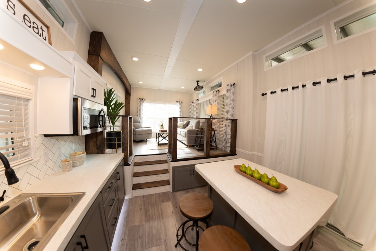 The kitchen is accompanied by a dining table with chairs that can also be used as an island