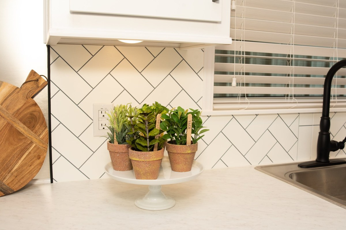 The kitchen backsplash has a beautiful zig-zag design make with white subway tiles