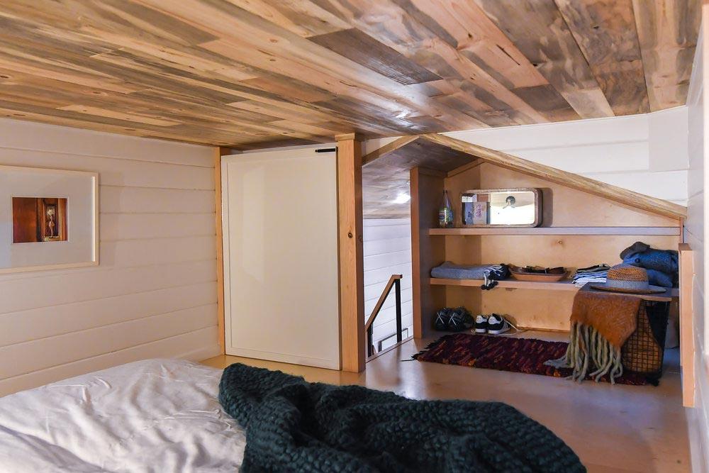 The loft bedroom has an open closet with custom built-in shelves